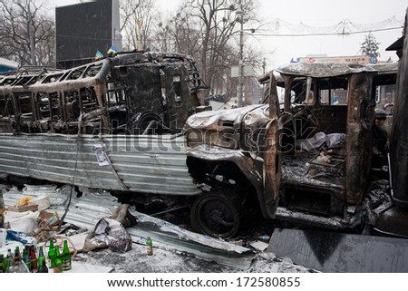 KYIV, UKRAINE - JAN 21: Broken and completely burned cars and buses on the massive barricades of occupying snow city during anti-government protest Euromaidan on January 21, 2014, in Kiev, Ukraine - stock photo