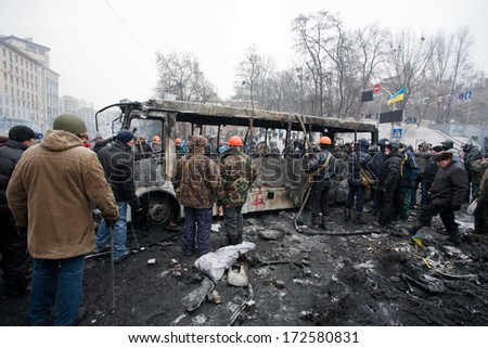 KYIV, UKRAINE - JAN 21: Many men in uniform and helmets overturned burned bus on the occupying street during anti-government protest Euromaidan on January 21, 2014, in center of Kiev, Ukraine.  - stock photo