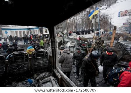 KYIV, UKRAINE - JAN 21: Moving activists walk past the barricades with police squads behind on the occupying snow street during anti-government protest Euromaidan on January 21, 2014, in Kiev, Ukraine - stock photo