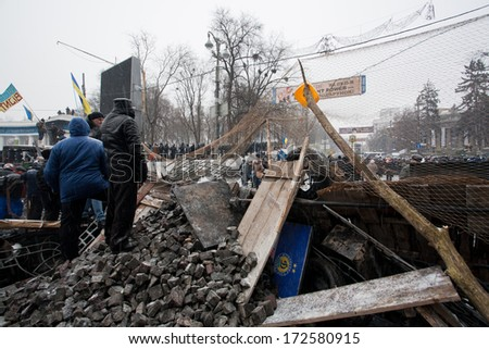 KYIV, UKRAINE - JAN 21: People watch police squad behind the barricades with bricks and wood during anti-government protest Euromaidan on winter street on January 21, 2014, in Kiev, Ukraine - stock photo