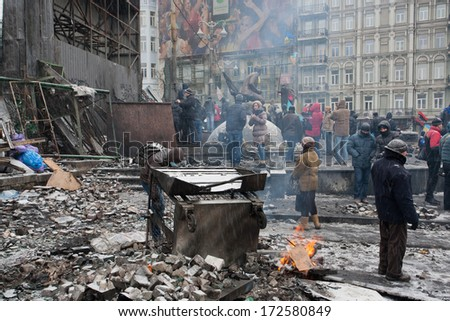 KYIV, UKRAINE - JAN 21: Protesters burn fire near the barricades after clashes with police on the destroyed street during anti-government protest Euromaidan on January 21, 2014, in Kiev, Ukraine.   - stock photo
