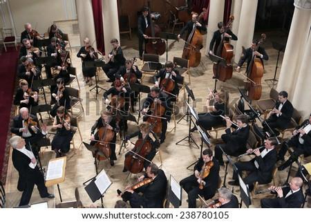 KYIV, UKRAINE - JAN 16: Violinist Dmitry Tkachenko, conductor Fedor Glushchenko and the National Symphony Orchestra of Ukraine on January 16, 2013 in Kyiv, Ukraine. - stock photo