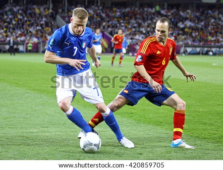 KYIV, UKRAINE - JULY 1, 2012: Ignazio Abate of Italy (L) fights for a ball with Andres Iniesta of Spain during their UEFA EURO 2012 Final game at Olympic stadium in Kyiv, Ukraine - stock photo