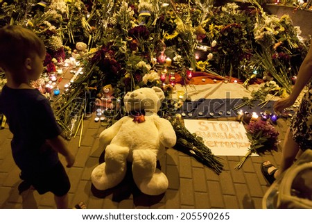KYIV, UKRAINE - JULY 17, 2014: People place flowers at Dutch embassy in Kyiv after Malaysia Airlines Boeing 777 originating in Amsterdam crashed in Eastern Ukraine - stock photo