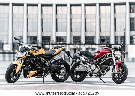 Kyiv, Ukraine - July 7th, 2015: Red motorcycle Ducati Monster and yellow Ducati Streetfighter at the city street. - stock photo