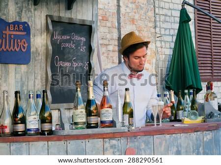 KYIV, UKRAINE - JUNE 8, 2015: Cute bartender pours sparkling wine in glasses behind the bar in outdoor restaurant on June 8, 2015. Ukrainian capital, Kiev has population near 2,900,200 people - stock photo