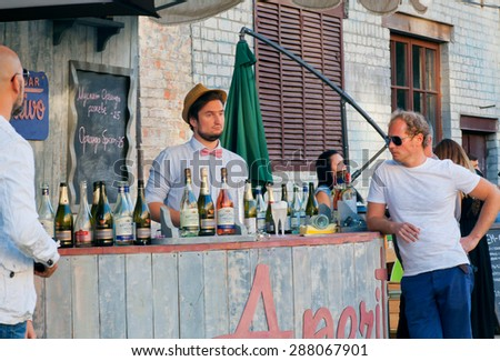 KYIV, UKRAINE - JUNE 8, 2015: Handsome bartender thinking about cocktails behind the bar counter in outdoor restaurant on June 8, 2015. Ukrainian capital, Kiev has population near 2,900,200 people - stock photo