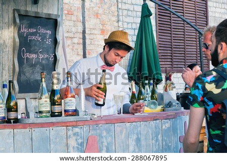 KYIV, UKRAINE - JUNE 8, 2015: Young bartender pours sparkling wine in glasses behind the bar in outdoor restaurant on June 8, 2015. Ukrainian capital, Kiev has population near 2,900,200 people - stock photo