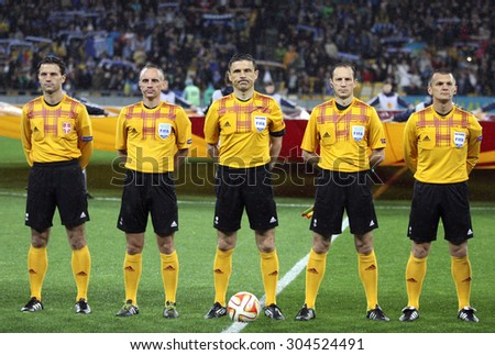 KYIV, UKRAINE - MAY 14, 2015: Referee Milorad Mazic (C) and his assistants before UEFA Europa League semifinal game between FC Dnipro and SSC Napoli at NSK Olimpiyskyi stadium - stock photo