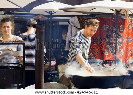 KYIV, UKRAINE - MAY 15: Sea-food cook preparing food in huge pan at outdoor party of Street Food Festival on May 15, 2016. Kiev is the 8th most populous city in Europe. - stock photo