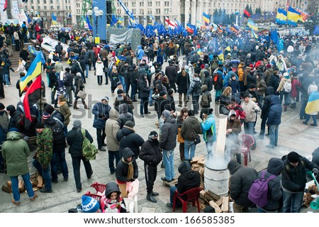 KYIV, UKRAINE - NOV 28: Crowd of people walking around the cold occupying street during two weeks of anti-government protest on November 28, 2013, in Kiev, Ukraine. - stock photo