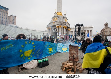 KYIV, UKRAINE - NOV 28: Young people with the flags and transparency standing on the cold occupying street during two weeks of anti-government protest on November 28, 2013, in Kiev, Ukraine. - stock photo