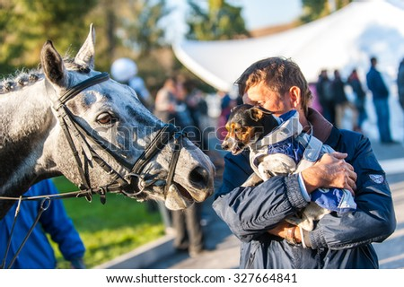 KYIV, UKRAINE - OCTOBER 10, 2015: A participant  of competitions in jumping demonstration caring a dog during international equestrian tournament - stock photo