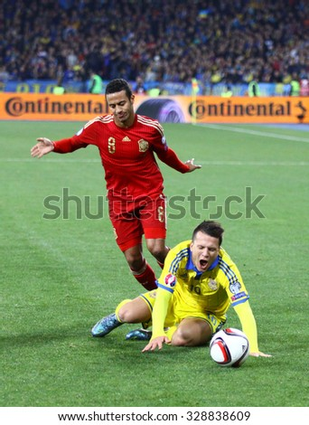 KYIV, UKRAINE - OCTOBER 12, 2015: Yevhen Konoplyanka of Ukraine (in yellow) fights for a ball with Thiago Alcantara of Spain during their UEFA EURO 2016 Qualifying game - stock photo