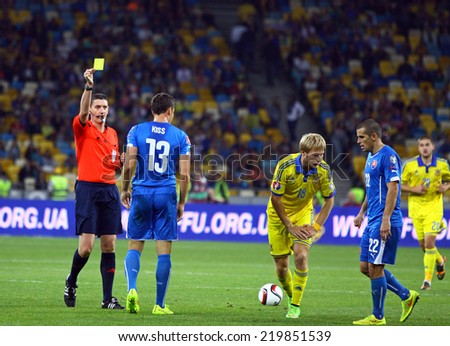 KYIV, UKRAINE - SEPTEMBER 8, 2014: Referee Craig Thomson of Scotland shows the yellow card during UEFA EURO 2016 Qualifying game between Ukraine and Slovakia - stock photo