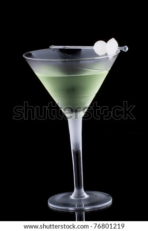 Kyoto cocktail in chilled martini glass over black background on reflection surface. Green color, gin, dry vermouth, melon liqueur,  garnished with marinated pearl onions. - stock photo