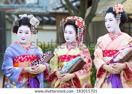 KYOTO - FEB 20, 2014: three young beautiful Japanese women called Maiko wear a traditional dress called Kimono on February 20, 2014 at Gion, Kyoto, Japan. - stock photo