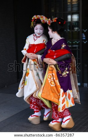 KYOTO - JAN 10: Two unidentified Geishas leave a building in the Gion district of Kyoto, Japan on January 10, 2010. Geishas are girls skilled in traditional Japanese arts. - stock photo