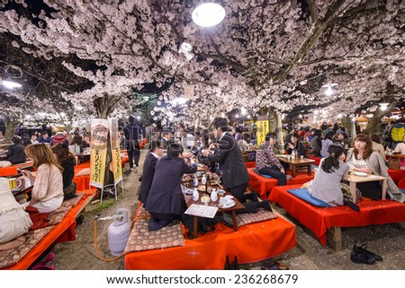 KYOTO, JAPAN - APRIL 3, 2014: Crowds enjoy the spring cherry blossoms by partaking in seasonal nighttime Hanami festivals in Maruyama Park.  - stock photo