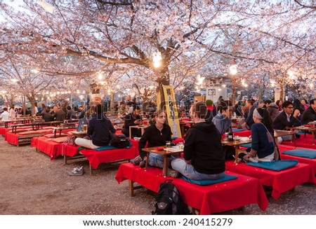 KYOTO, JAPAN - APRIL 8, 2014: People enjoy spring season by partaking in nighttime Hanami festivals in Maruyama Park. The annual festivals coincide with the seasonal blooming of the cherry blossoms.  - stock photo