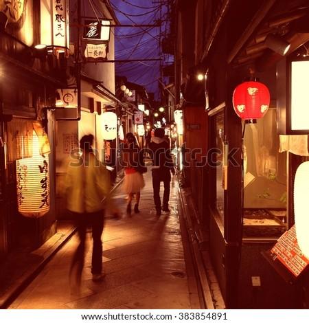 KYOTO, JAPAN - APRIL 16, 2012: Tourists visit Pontocho street in Kyoto, Japan. According to TripAdvisor, best restaurants in Kyoto are located in Pontocho. - stock photo