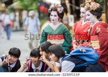 KYOTO, JAPAN - JUNE 10: Unidentified tourist women dress like a Maiko and take photo with children, Tourists usually makeup as Geishas (also known as Maiko) in Kyoto on June 10, 2015 in Japan - stock photo