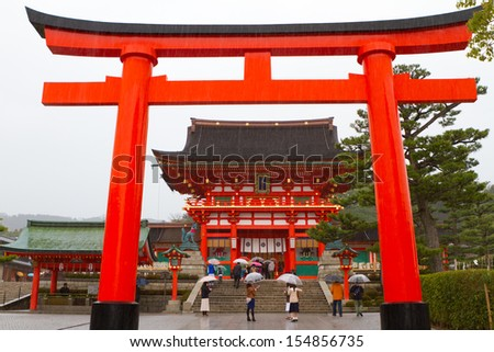 KYOTO, JAPAN - MARCH 18: A giant torii gate in front of the Romon Gate at Fushimi Inari Shrine's entrance on March 18, 2013 in Kyoto, Japan. This is the head shrine of Inari in Japan.  - stock photo
