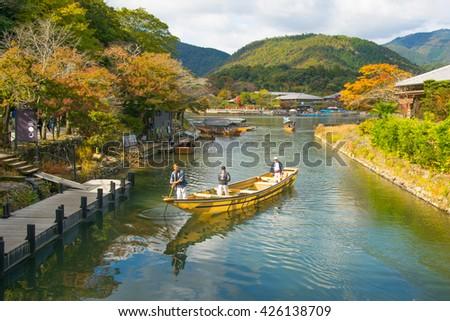 KYOTO, JAPAN - NOV 13, 2015: Traditional tourist boat pass on the Katsura river in the morning, Arashiyama Kyoto Japan - stock photo