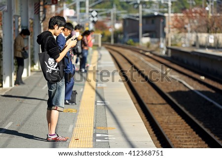 KYOTO, JAPAN - Nov 4: Unidentified people waiting for the train to homing at JR train in JR Umahori Station on November 4, 2015 in Kyoto, Japan - stock photo