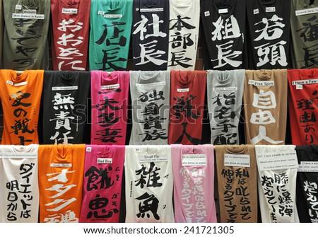 KYOTO, JAPAN - NOVEMBER 9, 2014: Colorful T-shirts are displayed at a souvenir shop. Text in Japanese is translated into English at a small paper. November 9, 2014 Kyoto, Japan - stock photo