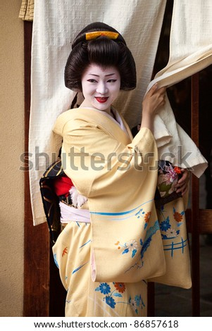 KYOTO, JAPAN - NOVEMBER 8: Geisha by the entrance to a teahouse in the Gion district on November 8, 2010 in Kyoto, Japan. Geisha perform ceremonies and entertain through classical music and dance. - stock photo