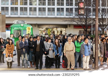 KYOTO, JAPAN, NOVEMBER 25, 2011: Pedestrians are waiting at the crosswalk in the Shibuya district in Tokyo, Japan - stock photo