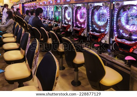 KYOTO, JAPAN, NOVEMBER 15, 2011: Some customers are gambling in a Pachinko hall, traditional Japanese Game in Kyoto, Japan - stock photo