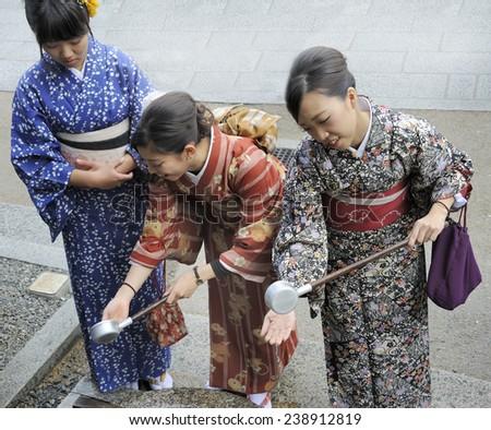 KYOTO,JAPAN-NOVEMBER 4, 2014; Three geishas cleaning their hands with holy water at a temple.November 4,2014 Kyoto, Japan - stock photo