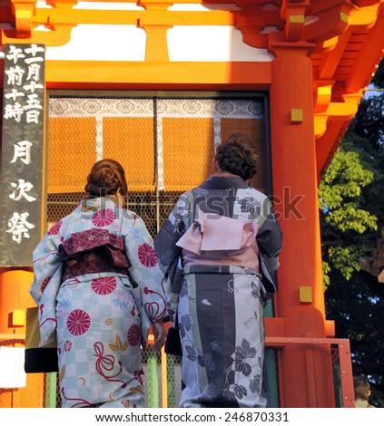 KYOTO, JAPAN - NOVEMBER 3, 2014: Two geisha's at sunset at the Enryaku-ji Temple. This is an Unesco World Heritage site.November 3, 2014 Kyoto, Japan  - stock photo