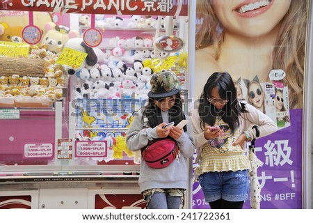 KYOTO,JAPAN-NOVEMBER 9, 2014; Two girls watching their mobile telephones at a shopping center.November 9, 2014 Kyoto, Japan - stock photo