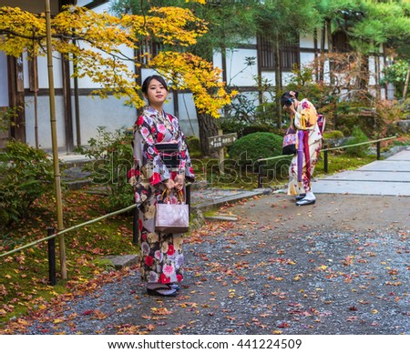 KYOTO, JAPAN - November, 18, 2014: Two japanese girls in traditional kimono, momiji season in Kyoto