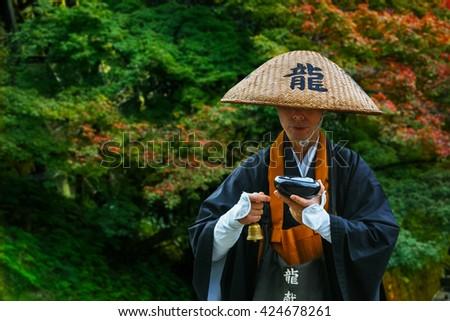KYOTO, JAPAN - NOVEMBER 22 2015: Unidentified Japnese monk prays for passing people in front of Kiyomizu-dera temple - stock photo