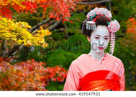 """KYOTO, JAPAN - NOVEMBER 22 2015: Unidentified """"Maiko"""" girl or apprentice Geisha is in a Japanese garden in autumn - stock photo"""