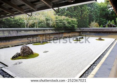 KYOTO,JAPAN-NOVEMBER 10, 2014: Zen Rock Garden in Ryoanji Temple, Kyoto, Japan. In the garden there are fifteen stones on white gravel. November 10, 2014 Kyoto, Japan - stock photo