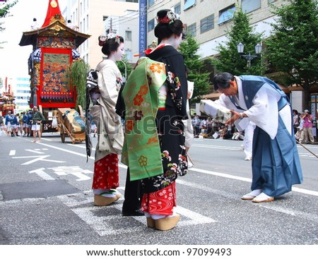 KYOTO - JULY 17: Two geishas receive a gift from a participant of the famous annual Gion Festival held on July 17 2010 in Kyoto, Japan. Geishas often participate in traditional celebrations. - stock photo