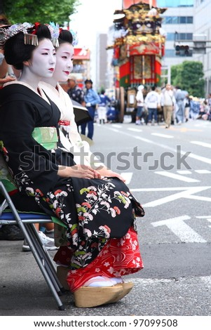 KYOTO - JULY 17: Two unidentified geishas participate on the famous Gion Festival held on July 17 2010 in Gion district, Kyoto, Japan. Geishas often participate on traditional japanese celebrations. - stock photo