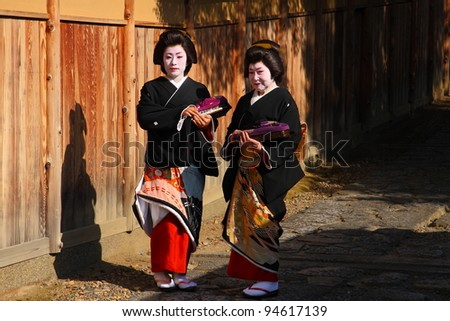 KYOTO - NOV 21: Unidentified geishas on a traditional street on November 21 2009 in Gion district, Kyoto, Japan. Geishas are skilled in traditional arts such as music, dance, singing and tea ceremony. - stock photo