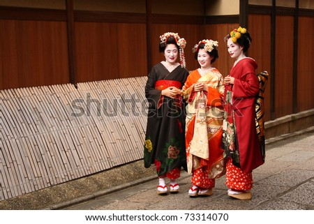 KYOTO - NOV 21: Unidentified Geishas walking by an old street and speaking on November 16, 2010 in Gion district, Kyoto, Japan. Geishas are girls skilled in traditional japanese arts. - stock photo