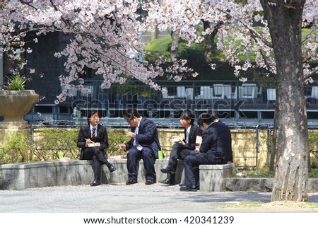 KYOTO, OSAKA - April 6: Four unidentified young japanese men having lunch under blossoming cherry trees on April 6th, 2016. Osaka and Tokyo are the largest business centers of Japan. - stock photo