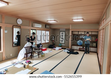 KYOTO, TOKYO - OCTOBER 10, 2015: Woman Helps with Wedding Kimono before Traditional Japanese Wedding in Shrine. Bride and Groom