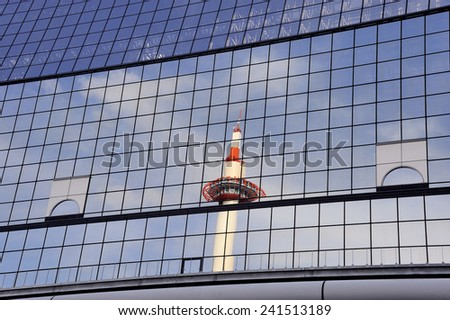 Kyoto Tower mirrored in glass steel building. Taken at Kyoto railway station, Japan. - stock photo
