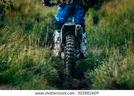 "Kyshtym, Russia - July 26, 2015: A motocross racer is riding on a footpath during the race Urals Cup of Enduro ""Forest watch"", Kyshtym, Russia - July 26, 2015"