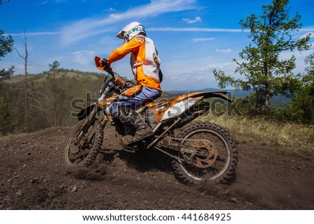 Kyshtym, Russia - June 19, 2016: rider rides on mountain, dirt and stones from under wheels during Ural Cup in Enduro