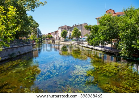 L'Isle-Sur-La-Sorgue, a small typical town in Provence, France. Beautiful village, with view on roof and landscape, small cafe and restaurants. - stock photo